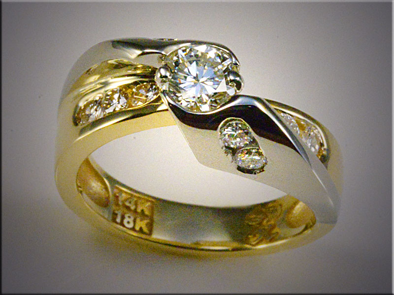 14K white gold diamond sectionwith 18K yellow gold base. Smaller diamonds set in channels, center diamond set partial bezel and part prongs.  Designed and made by Ron Litolff