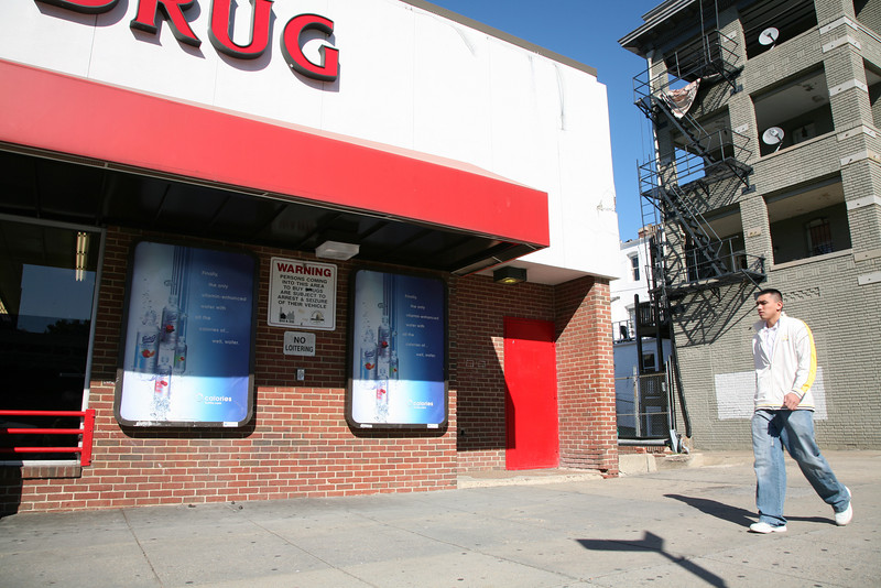 """Adams Morgan is an eclectic neighborhood. This CVS Drugstore posts side by side an advertisement for vitamin enhanced water as well as a sign warning that """"Persons coming into this area to buy drugs are subject to arrest & seizure of their vehicle."""" One assumes the drugs inside the store are exempt."""