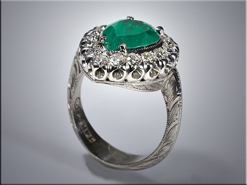 "p528<br /> 14K white gold vintage style fashion ring with pear shaped emerald in center, surrounded by round diamonds set in a ""fishtail"" style setting. Designed and made by Ron Litolff."
