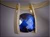 14K yellow gold contemporary pendant set with cushion shaped sapphire and accent diamonds