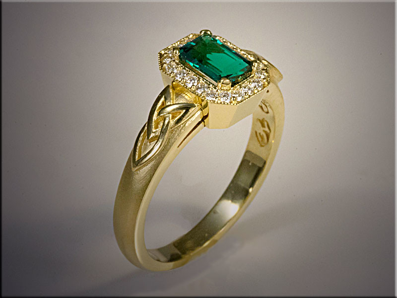 18K yellow gold custom emerald ring with ideal cut diamonds.  High polished modified Trinity Knot over satin finished band.  Designed and made by Ron Litolff