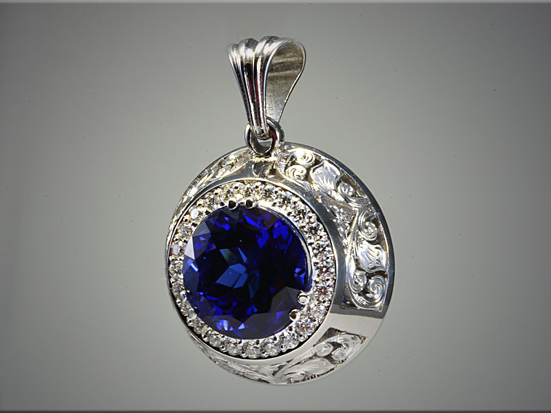 p531<br /> 14K white gold pendant mounting for a round tanzanite, surrounded by ideal cut diamonds with hand engraved panels on the sides.  Designed and made by Ron Litolff.