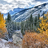 Fall colors on river and snowy mountains
