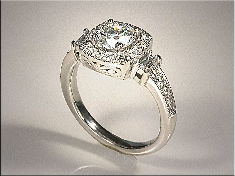 Platinum custom mounting with 1ct center diamond with cushion shaped halo.  Bead and bright cut style with baguette accents.  Designed and made by Ron Litolff