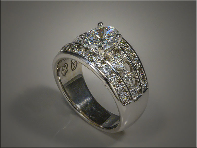 14K white gold remount of customers oval diamond.  With 3 princess cut diamonds on each side, and a channel set row of diamonds on each side of ring.  Designed and made by Ron Litolff