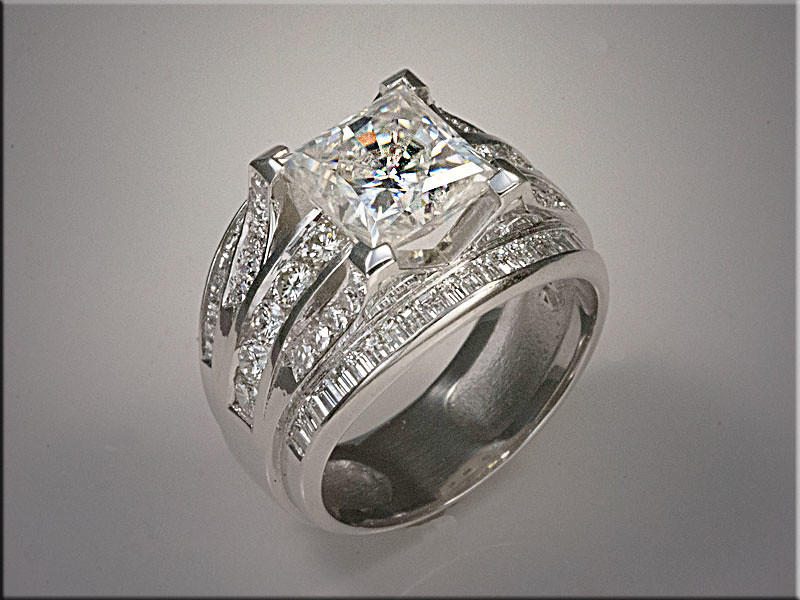 Platinum custom gents mounting with princess cut center, rounds through center section in channel and bead and bright cut, with channel set baguettes diamonds on outer edge.  Designed and made by Ron Litolff