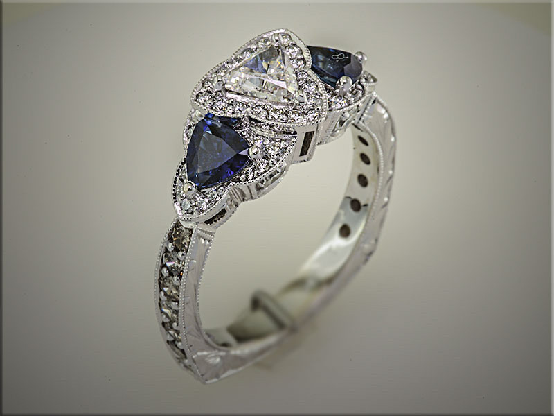 14K white gold halo style mounting for customers diamonds, with 2 trillion shaped sapphires.  Deisgned and made by Tim Frank.