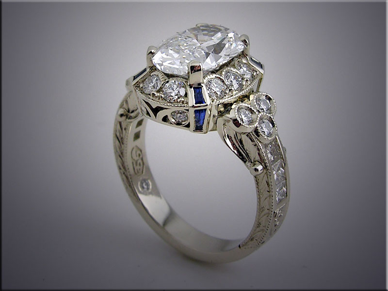 14K white gold mounting set with oval center diamond, smaller accent diamonds and tapered bauette sapphires