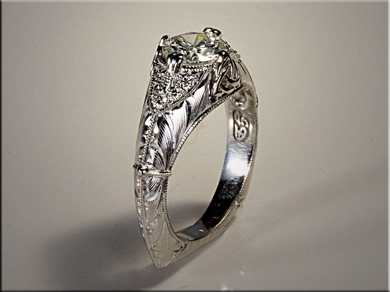 14K white gold custom engagement ring with center diamond being held in by prongs and Trinity Knot.  Designed and made by Ron Litolff.  Hand engraved by Tim Frank