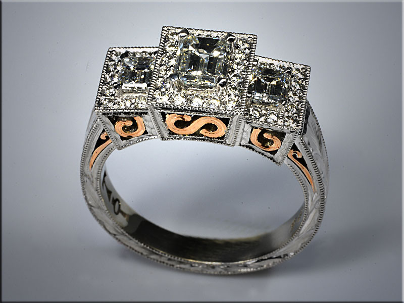 p526<br /> 14K white gold 3 section engagement ring with emerald cut diamonds surrounded by ideal cut round diamonds.  Ring has 14K rose gold scroll accents.  Designed and made by Tim Frank.