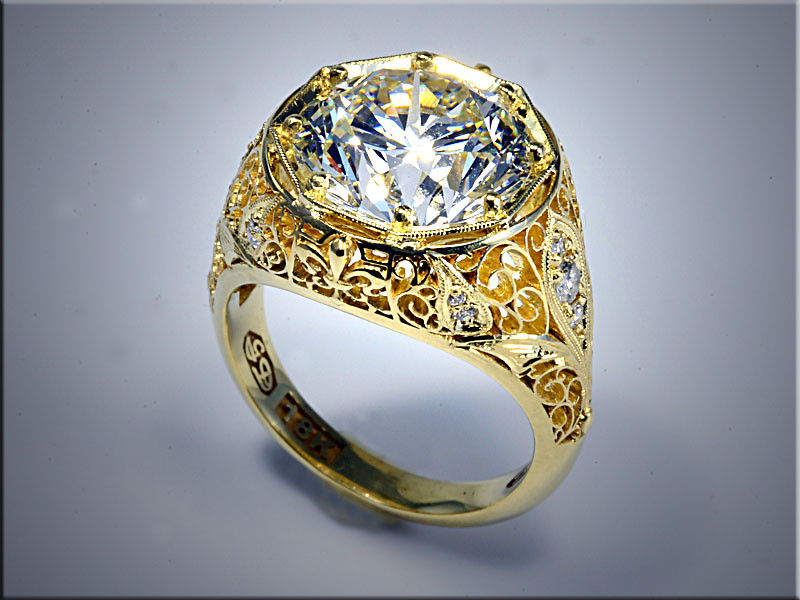 18K Yellow Gold custom mounting for 5ct Round Brilliant Cut Diamond.  Very fine Filagree on sides with diamond panels.  Designed and made by Ron Litolff.
