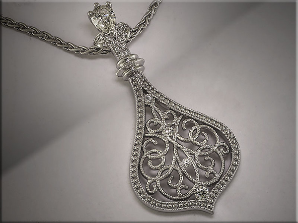 14K white gold customer inspired genie bottle with scroll pattern and pear shape diamond in bail.  Designed and made by Ron Litolff