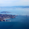 Aerial view through a window of commercial airliner of Golden Gate Bridge and Alcatraz in San Francisco Bay.