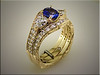 14K yellow gold custom set with sapphire center and diamonds on sides and bands.  Designed and made by Tim Frank