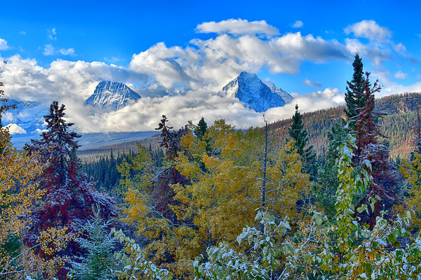 Two mountains and snow filled colorful trees