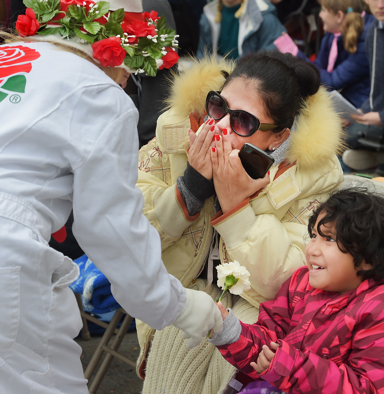 """. A Tournament volunteer giving a rose to a young girl at the 128th Rose Parade \""""Echoes of Success\"""". (Photo by Walt Mancini/SCNG)"""