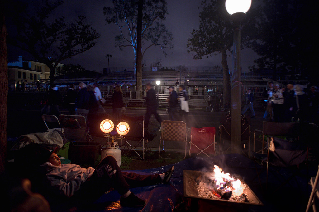 . Michael Flores, 16, of Alhambra, who reserved a spot for his family along Orange Grove Boulevard on New Years morning, sleeps as crowds begin to fill the streets before the start of the 2017 Rose Parade in Pasadena, Calif. on Monday, Jan. 2, 2017. (Photo by Sarah Reingewirtz, Pasadena Star-News/SCNG)