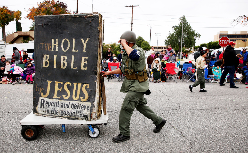 . A man pushes a large Bible along the parade route before the 128th Rose Parade in Pasadena, Calif. on Monday, Jan. 2, 2017. (Photo by Trevor Stamp)
