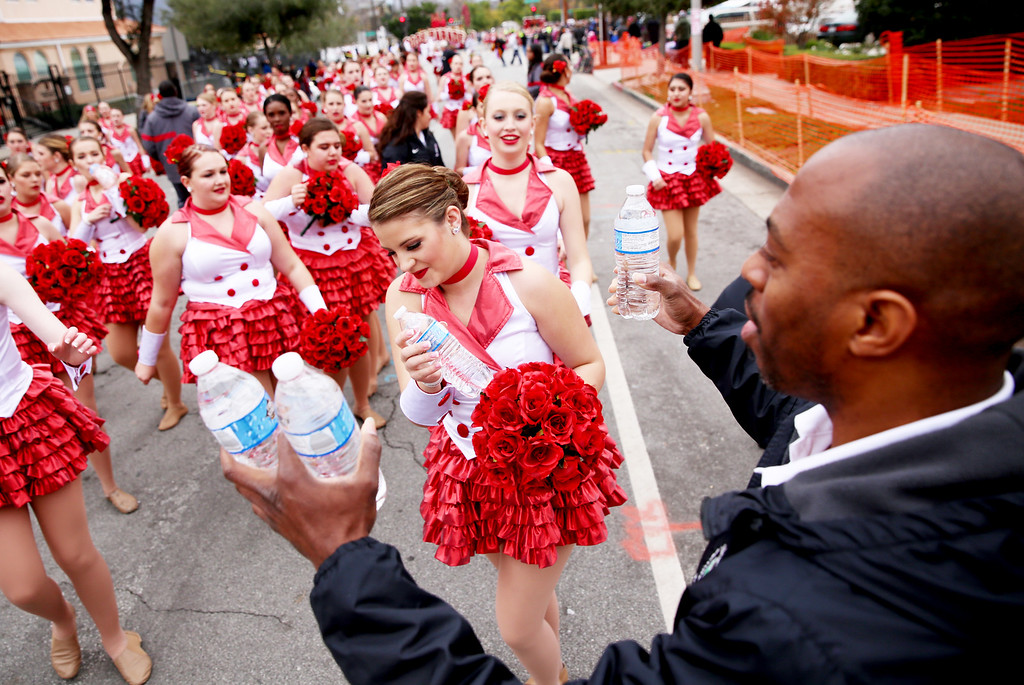 . Corey Campbell, right, hands out water to participants reaching the end of the  128th Rose Parade in Pasadena, Calif. on Monday, Jan. 2, 2017. (Photo by Trevor Stamp)