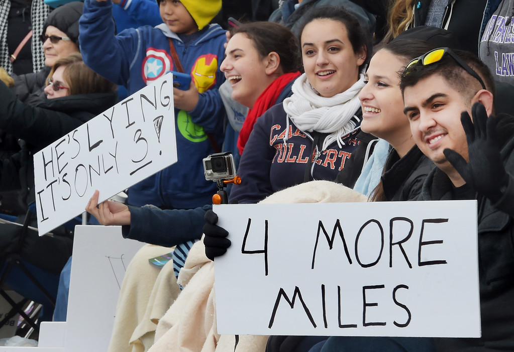 ". A sign greeting band members that there is 4 MORE MILES to the end, and another sign saying HE�S LYING   IT�S ONLY 3! at the 128th Rose Parade ""Echoes of Success\"". (Photo by Walt Mancini/SCNG)"