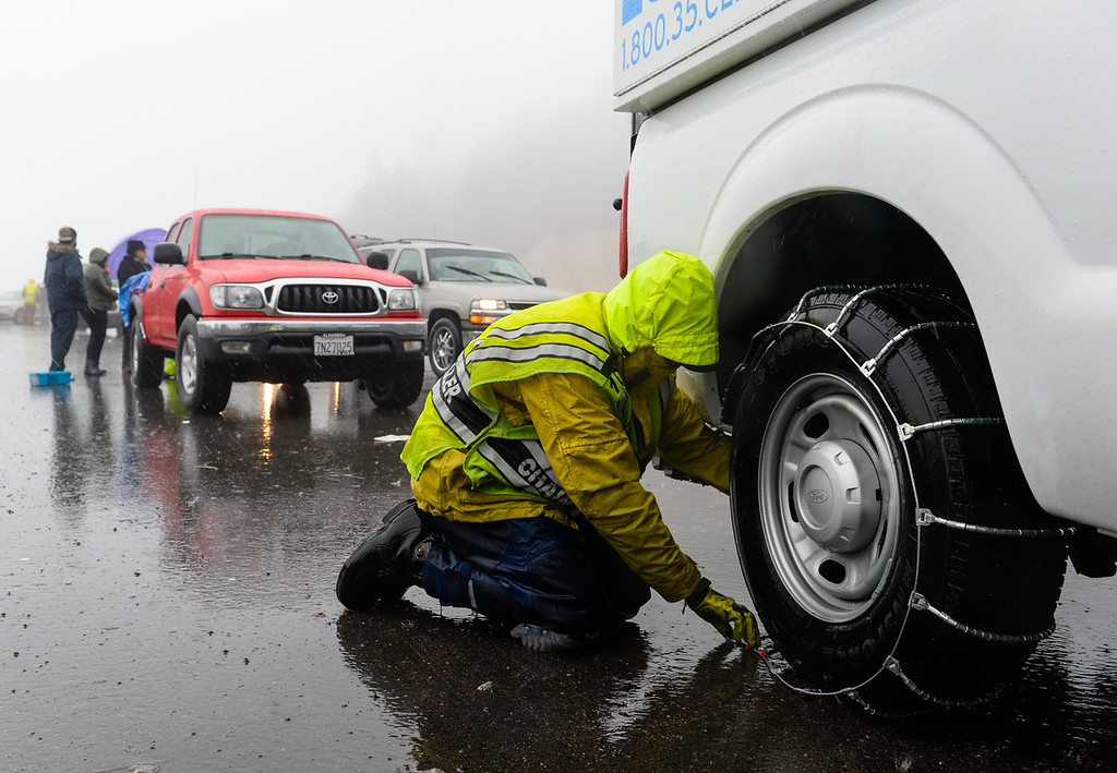 . Motorists chain up at a snow chain control check point near Lake Gregory Drive in the San Bernardino National Forest on Thursday, Jan. 12, 2017. A storm brought rain and snow to the Inland Empire. (Photo by Rachel Luna/The Sun, SCNG)