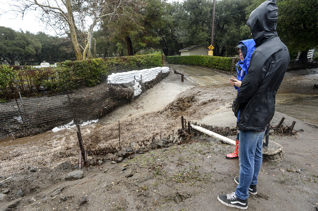 . Residents watch water and mud flow along Iron Canyon road in Santa Clarita Sunday as heavy rain falls in the area.   (Photo by David Crane, Los Angeles Daily News/SCNG)