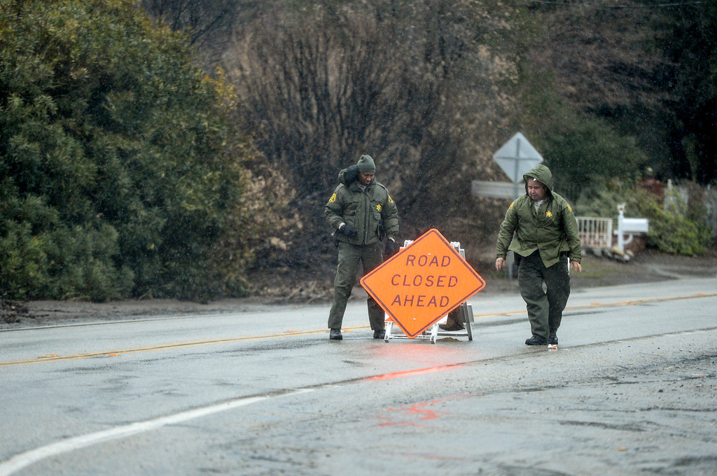 . Sheriff deputies place a road closed sign along Sand Canyon road near Placerita Canyon road in Santa Clarita Sunday morning as heavy rain falls in the area.  Evacuations were ordered in the area.   (Photo by David Crane, Los Angeles Daily News/SCNG)