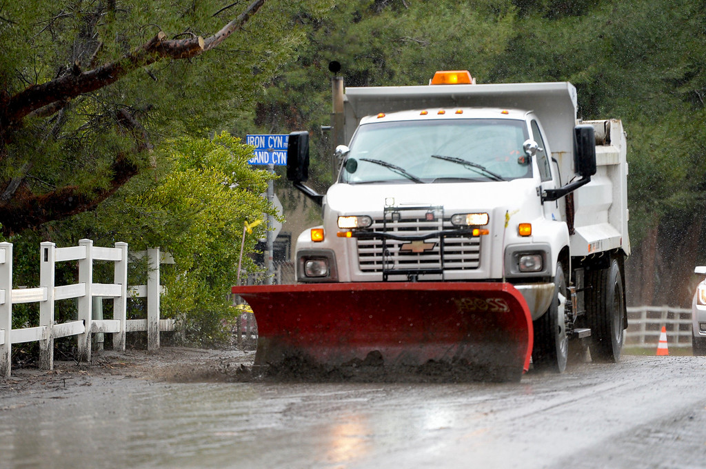 . A truck keeps mud and rocks from blocking Sand Canyon road in Santa Clarita Sunday as heavy rain falls in the area.   (Photo by David Crane, Los Angeles Daily News/SCNG)