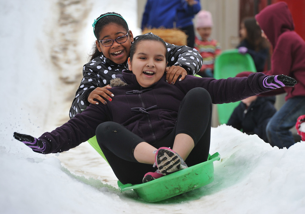 . Soliel Gonzalez, front and Zoe Smith slide down the snow at Bethany Lutheran School where 10 tons of snow was delivered Thursday to  thank students for a successful jog-a-thon.  Long Beach January 30, 2014. (Photo by Brittany Murray / Press Telegram)