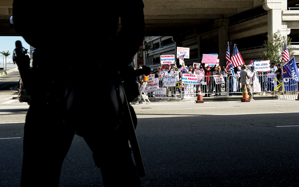 . Los Angeles police department officer stands ready between supporters of President Donald J. Trump and anti-Trump protestors at Tom Bradley International Terminal, Los Angeles International Airport in Los Angeles on Saturday, February 04, 2017. (Photo by Ed Crisostomo, Los Angeles Daily News/SCNG)