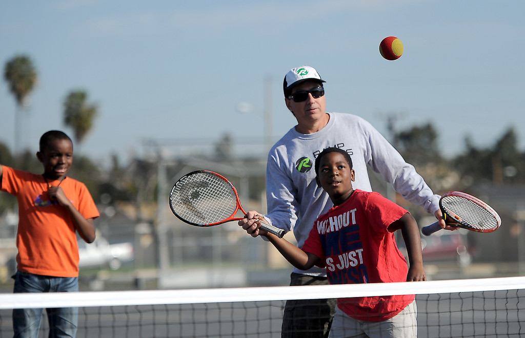 . Mekhi Crawford gets help from coach Rick Buchta, CEO of Ramp Tennis, at Leapwood Elementary Wednesday as part of an outreach program by a local tennis academy Ramp Tennis in Carson , CA. on Wednesday, February 05, 2014. (Photo by Sean Hiller/ Daily Breeze).
