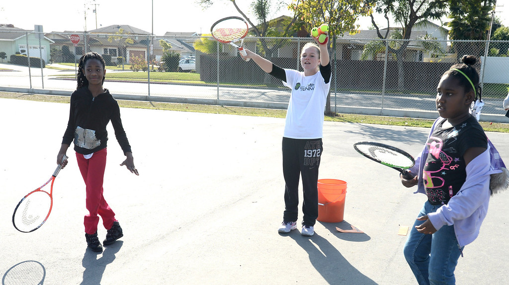 . Riley McQuaid of Ramp Tennis, helps students at Leapwood Elementary Wednesday as part of an outreach program by a local tennis academy Ramp Tennis in Carson , CA. on Wednesday, February 05, 2014. (Photo by Sean Hiller/ Daily Breeze).