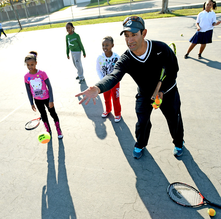 . Marc Lucero, tennis director at Ramp Tennis, helps students at Leapwood Elementary Wednesday as part of an outreach program by a local tennis academy Ramp Tennis in Carson , CA. on Wednesday, February 05, 2014. (Photo by Sean Hiller/ Daily Breeze).