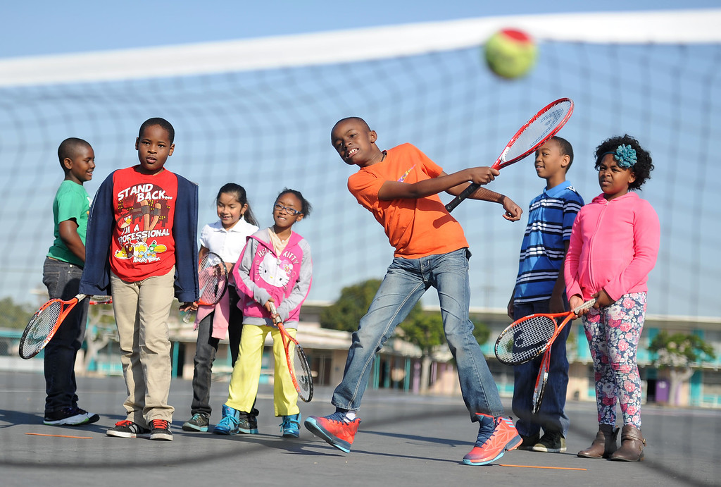 . Andy Mandela, 9, center, and fellow students at Leapwood Elementary take a swing at tennis lessons Wednesday as part of an outreach program by a local tennis academy Ramp Tennis in Carson , CA. on Wednesday, February 05, 2014. (Photo by Sean Hiller/ Daily Breeze).