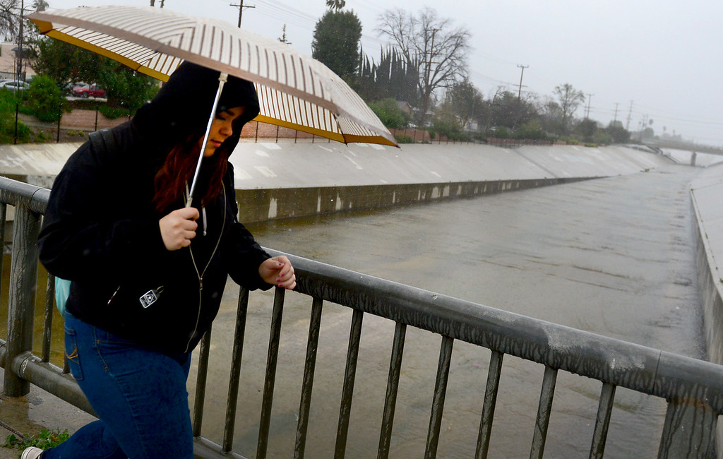 . A woman walks past the L.A. River as it passes Owensmouth Ave. in Canoga Park on Friday Morning, February 17, 2017.  (Photo by Dean Musgrove, Los Angeles Daily News/SCNG)
