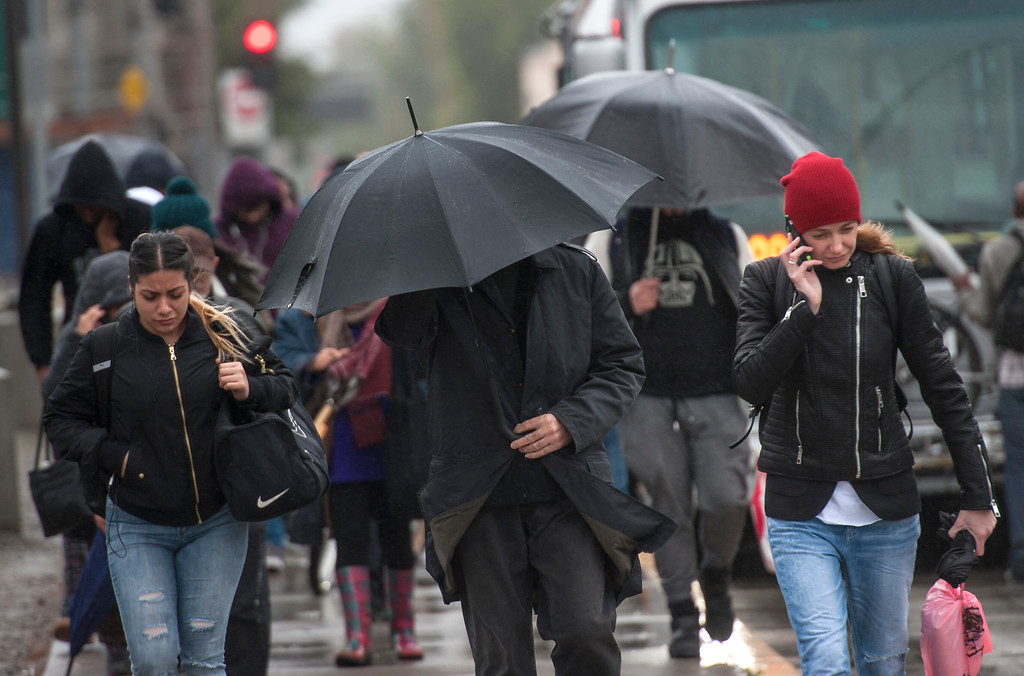 . People take cover as they navigate through the wind and rain in North Hollywood on Friday, February 17, 2017. (Photo by Ed Crisostomo, Los Angeles Daily News/SCNG)