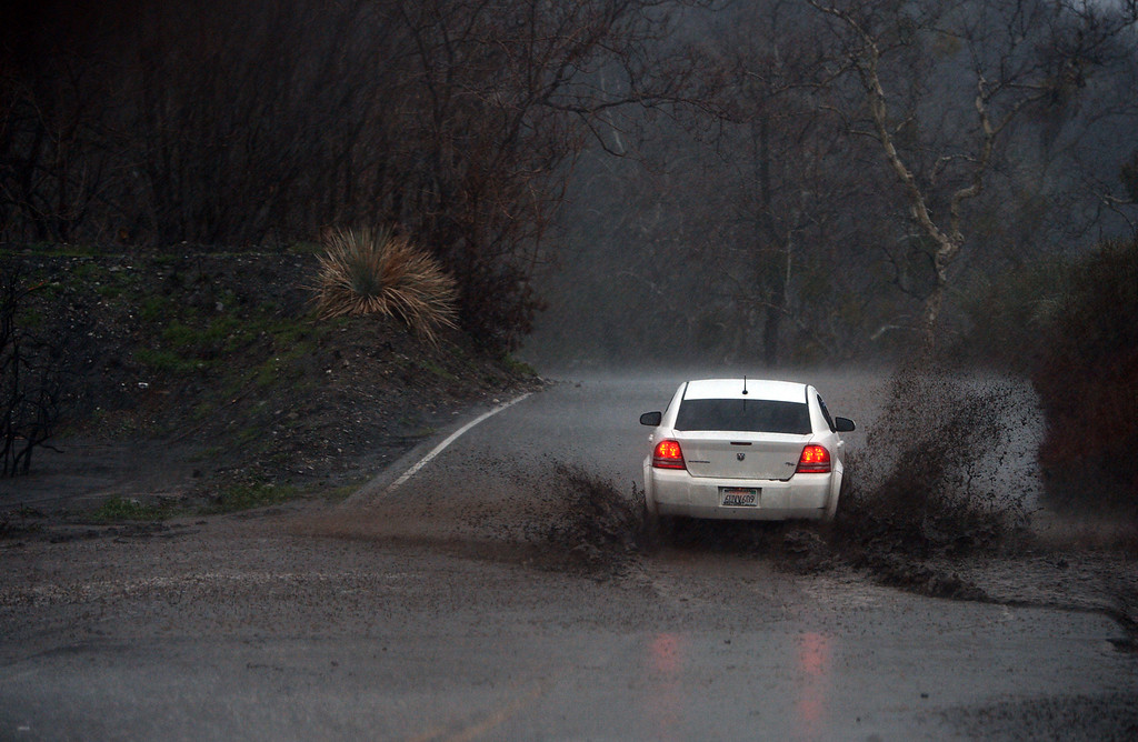 . A car crosses rising rain run-off on Lytle Creek Road in the Blue Cut Fire burn area in Lytle Creek, CA., Friday, February 17, 2017. (Staff photo by Jennifer Cappuccio Maher/The Sun/SCNG)