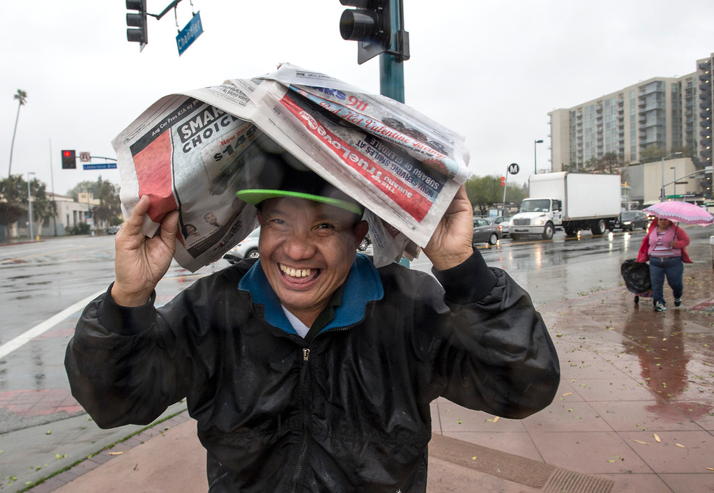 . Napoleon Requinto, takes cover as he navigates through the wind and rain in North Hollywood on Friday, February 17, 2017. (Photo by Ed Crisostomo, Los Angeles Daily News/SCNG)