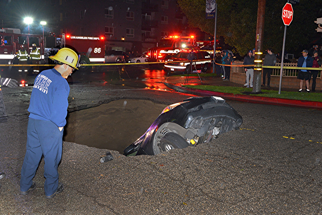 . Two vehicles fell into a 20-foot sinkhole in Studio City Friday, February 17, 2017 and firefighters had to rescue at least one trapped person.  The person that was rescued was taken to a hospital in an unknown condition, according to Erik Scott of the Los Angeles Fire Department.  Firefighters were sent at 8:16 p.m. to the sinkhole in the 4200 block of North Laurel Canyon Boulevard, two blocks south of Moorpark Street, Scott said.  (Photo by Rick McClure for the Los Angeles daily News/SCNG)