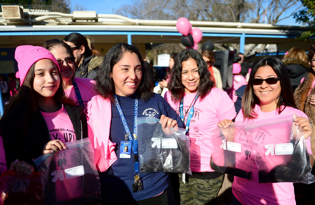 . During its outdoor school assembly, 57 students, teachers, and parents had their ponytails cut off by professional hair stylists from the community on Friday, February 24, 2017.  The fourth annual �Pony Up Cut-A-Thon� event at Serrania Charter for Enriched Studies elementary school included neighborhood middle school, Woodland Hills Academy.  The hair will be donated and made into wigs to help people with cancer.  Educators and students show their cut hair.  (Photo by Dean Musgrove, Los Angeles Daily News/SCNG)