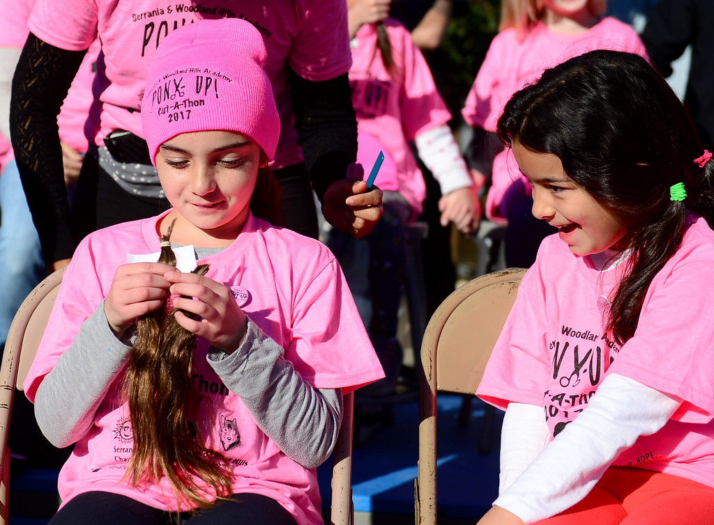 . Another student reacts as Abigail Berg, who turned eight today, looks at her two pony tails that were just cut.  During its outdoor school assembly, 57 students, teachers, and parents had their ponytails cut off by professional hair stylists from the community on Friday, February 24, 2017.  The fourth annual �Pony Up Cut-A-Thon� event at Serrania Charter for Enriched Studies elementary school included neighborhood middle school, Woodland Hills Academy.  The hair will be donated and made into wigs to help people with cancer.  (Photo by Dean Musgrove, Los Angeles Daily News/SCNG)