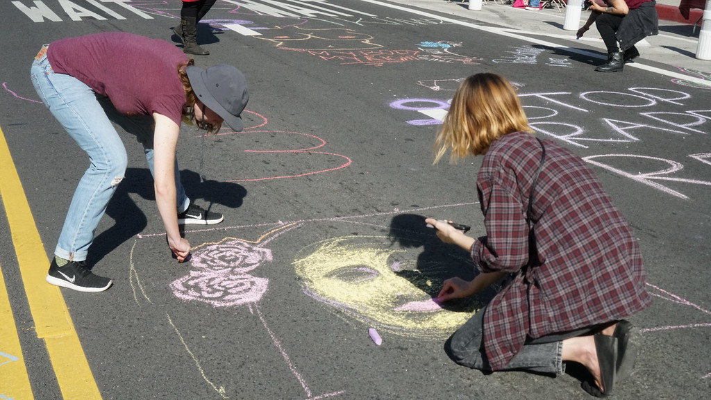 ". Lamb Chamberlin (right), 28, of Los Angeles, works on a chalk drawing on Los Angeles Street just before the start of the International Women\'s Strike rally outside the federal building downtown. Chamberlin said it was based on artist Shepard Fairey\'s ""We the People\"" poster. (Photo by Matthew Carey/Special to the Los Angeles Daily News)"