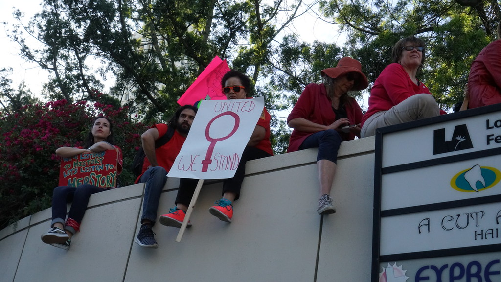 . Some who attended the International Women\'s Strike rally downtown got a bird\'s eye view of the event from a wall along Los Angeles Street. (Photo by Matthew Carey/Special to the Los Angeles Daily News)