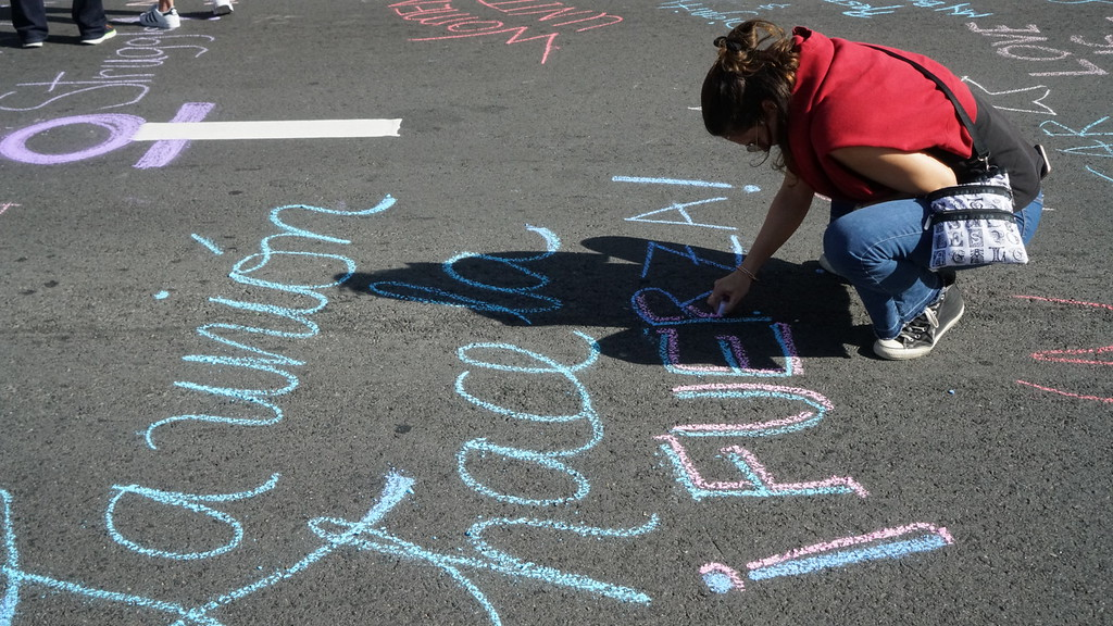 ". Ana Isabel Mercado, 35, of Koreatown, works on a chalk drawing before the start of the International Women\'s Strike rally in downtown Los Angeles. She wrote, ""La unión hace la fuerza\"" (\""unity brings Strike\""). (Photo by Matthew Carey/Special to the Los Angeles Daily News)"