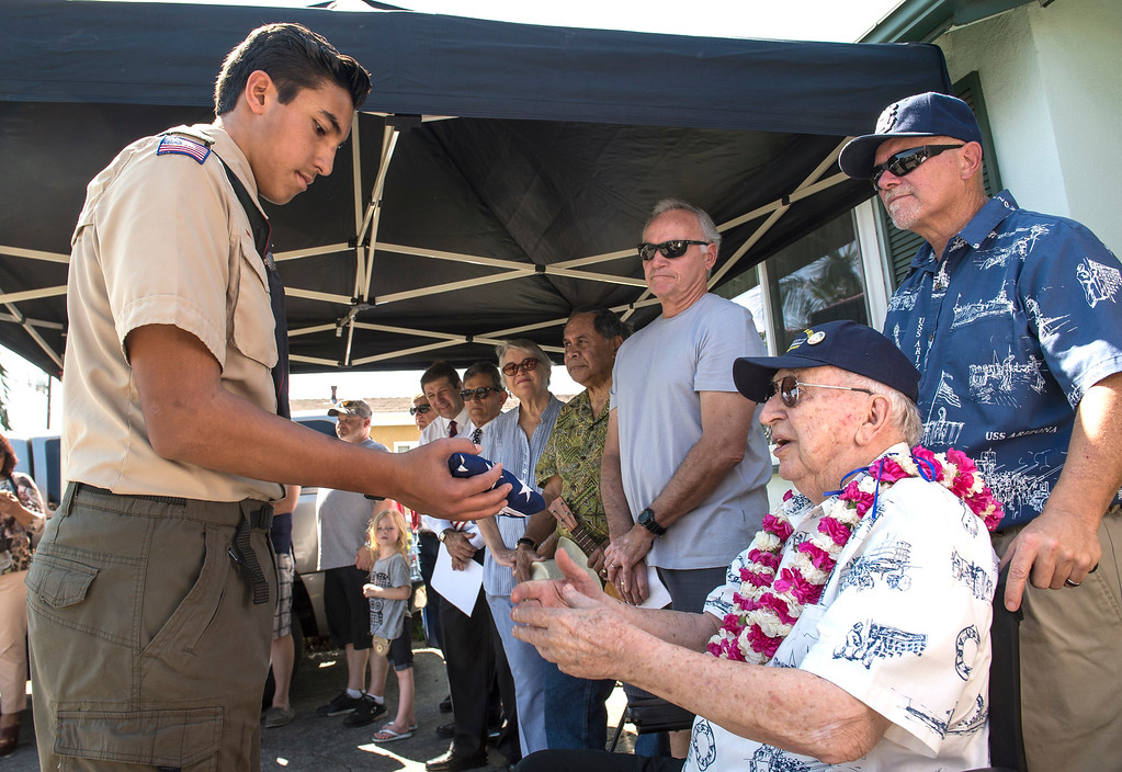 . World War II veteran Lauren Bruner, 96, gives the American Flag to Josiah Gil, 15, Boy Scout Troop 749, during a flag-raising ceremony in La Mirada on Saturday, March 11, 2017. Lauren Bruner is one of the remaining survivors of the Pearl Harbor attack on Dec. 7, 1941. Bruner was stationed on the USS Arizona. (Photo by Ed Crisostomo, Los Angeles Daily News/SCNG)
