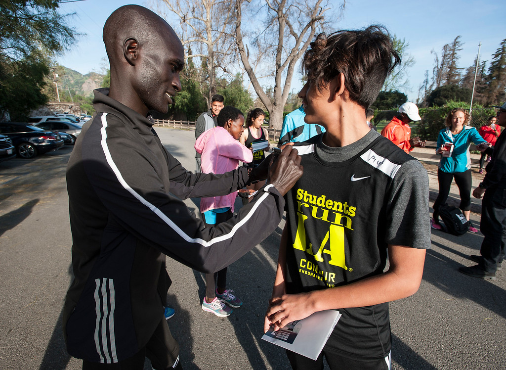. Julio Perez, 14, Students Run LA, smiles as he gets an autograph from elite marathon runner Willy Koitile, left, of Kenya, after a short training run at Griffith Park in Los Angeles on Friday, March 17, 2017. (Photo by Ed Crisostomo, Los Angeles Daily News/SCNG)