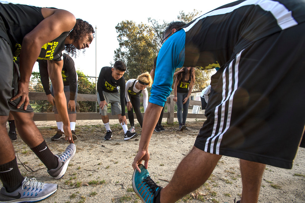 . Justin Malone, left, 18, Students Run LA, stretches before a training run with elite marathon runners from Kenya at Griffith Park in Los Angeles on Friday, March 17, 2017. (Photo by Ed Crisostomo, Los Angeles Daily News/SCNG)