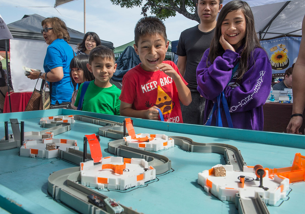 . Zoe Ngann, right, 11, of Rowland Heights, and her brothers Timothy, center, 9, and Zachary, 6, react as they play the Hex Bug Challenge race during The Annual West Covina Cherry Blossom Festival in West Covina on Saturday, March 18, 2017. (Photo by Ed Crisostomo, Los Angeles Daily News/SCNG)