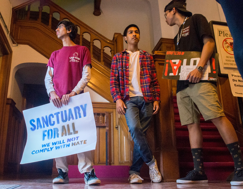 . Vijay Beniwal, left, Jonathan Tin, center and Khody Chhim, right, stands in the doorway before the start of the People\'s State of the City of Long Beach is seen Wednesday, April 5, 2017. (Photo by Thomas R. Cordova, Press-Telegram/SCNG)
