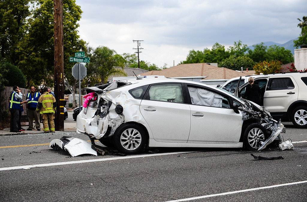 . Police investigate the scene of a crash involving a Toyota Prius and a school bus with children on board at 36th Street and Waterman Avenue in San Bernardino, Calif. on Tuesday, April 18, 2017. Officials stated there were no injuries in the crash, and students were evacuated from the bus because of a fuel leak. (Photo by Rachel Luna, The Sun/SCNG)